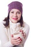 Mujer sonriente en el sombrero hecho punto que sostiene la taza de bebida Imagen de archivo libre de regalías