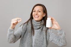 Mujer sonriente en el suéter gris, tabletas de la medicación del control de la bufanda, píldoras de aspirin en la botella aislada imagen de archivo libre de regalías