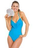 Mujer sonriente en el traje de baño que sostiene la fan de dólares Imagenes de archivo