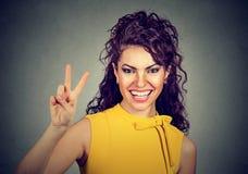 Mujer sonriente en el vestido amarillo que muestra la victoria o el signo de la paz Fotografía de archivo
