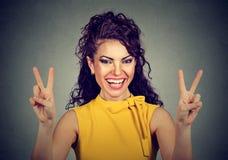 Mujer sonriente en el vestido amarillo que muestra la victoria o el signo de la paz Imagen de archivo libre de regalías