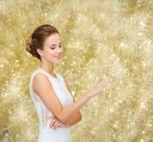 Mujer sonriente en el vestido blanco con el anillo de diamante Imagen de archivo