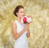 Mujer sonriente en el vestido blanco con el ramo de rosas Fotos de archivo libres de regalías