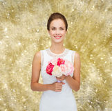 Mujer sonriente en el vestido blanco con el ramo de rosas Foto de archivo