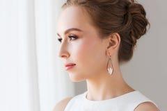 Mujer sonriente en el vestido blanco con joyería de la perla Fotografía de archivo