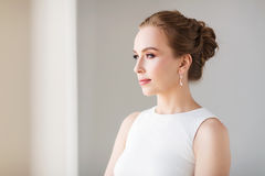 Mujer sonriente en el vestido blanco con joyería del diamante Imagenes de archivo