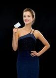 Mujer sonriente en el vestido de noche que sostiene la tarjeta de crédito Fotos de archivo libres de regalías