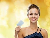 Mujer sonriente en el vestido de noche que sostiene la tarjeta de crédito Foto de archivo libre de regalías