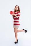 Mujer sonriente en el vestido que sostiene la caja de regalo Imagenes de archivo