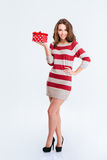 Mujer sonriente en el vestido que sostiene la caja de regalo Imagen de archivo