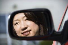 Mujer sonriente en espejo de coche imagen de archivo libre de regalías