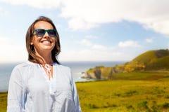 Mujer sonriente en gafas de sol sobre la costa de Big Sur foto de archivo