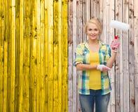 Mujer sonriente en guantes con el rodillo de pintura Imágenes de archivo libres de regalías
