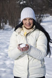 Mujer sonriente en invierno con una bola de nieve Imagen de archivo