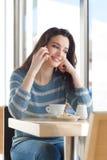 Mujer sonriente en la barra que tiene una llamada de teléfono Imagen de archivo