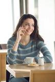 Mujer sonriente en la barra que tiene una llamada de teléfono Foto de archivo