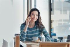 Mujer sonriente en la barra que tiene una llamada de teléfono Fotografía de archivo