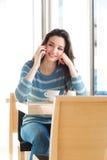 Mujer sonriente en la barra que tiene una llamada de teléfono Imagen de archivo libre de regalías