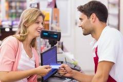 Mujer sonriente en la caja registradora que paga con la tarjeta de crédito Foto de archivo libre de regalías