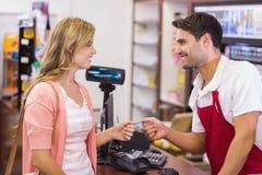 Mujer sonriente en la caja registradora que paga con la tarjeta de crédito Fotos de archivo