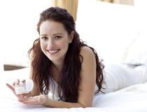 Mujer sonriente en la cama que toma píldoras Fotografía de archivo libre de regalías