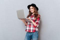 Mujer sonriente en la camisa de tela escocesa que se coloca y que trabaja en el ordenador portátil Fotografía de archivo libre de regalías