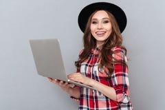 Mujer sonriente en la camisa de tela escocesa que sostiene el ordenador portátil Fotografía de archivo