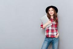 Mujer sonriente en la camisa de tela escocesa que sostiene el ordenador portátil y que mira lejos Fotografía de archivo libre de regalías