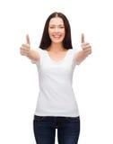 Mujer sonriente en la camiseta blanca que muestra los pulgares para arriba Imagen de archivo libre de regalías