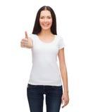 Mujer sonriente en la camiseta blanca que muestra los pulgares para arriba Foto de archivo libre de regalías