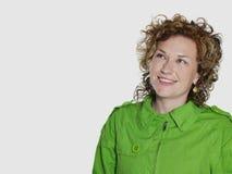 Mujer sonriente en la chaqueta verde que mira Copyspace Imágenes de archivo libres de regalías