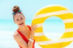 Mujer sonriente en la costa que muestra salvavidas inflable amarillo imagenes de archivo