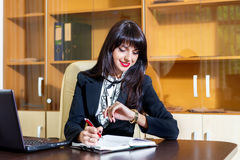 Mujer sonriente en la oficina que mira su reloj Fotografía de archivo libre de regalías