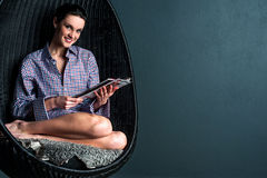 Mujer sonriente en la revista de la lectura de la silla de la burbuja Imagen de archivo