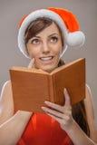 Mujer sonriente en la ropa de Santa Claus con el libro Imagen de archivo libre de regalías