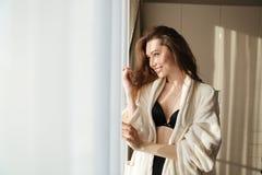 Mujer sonriente en la ropa interior y la albornoz que se colocan cerca de la ventana Imagen de archivo libre de regalías