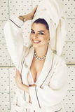 Mujer sonriente en la toalla, el traje y la joyería blancos Imagen de archivo libre de regalías