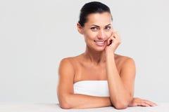 Mujer sonriente en la toalla que se sienta en la tabla Foto de archivo libre de regalías