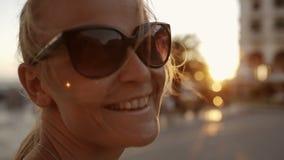 Mujer sonriente en las gafas de sol al aire libre durante puesta del sol metrajes