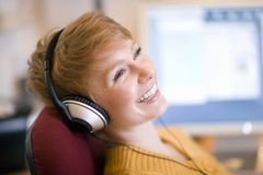 Mujer sonriente en los auriculares Foto de archivo libre de regalías