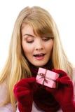 Mujer sonriente en los guantes de lana que abren el regalo para la Navidad o la otra celebración Foto de archivo