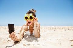 Mujer sonriente en los vidrios de la piña que toman el selfie en la playa arenosa Fotos de archivo libres de regalías