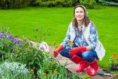 Mujer sonriente en pañuelo y botas rojas que planta las flores Fotos de archivo libres de regalías