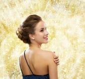 Mujer sonriente en pendientes que llevan del vestido de noche Fotografía de archivo libre de regalías