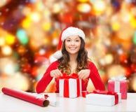 Mujer sonriente en regalos del embalaje del sombrero del ayudante de santa Fotos de archivo libres de regalías