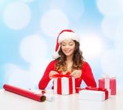 Mujer sonriente en regalos del embalaje del sombrero del ayudante de santa Imágenes de archivo libres de regalías