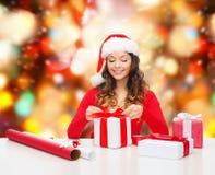 Mujer sonriente en regalos del embalaje del sombrero del ayudante de santa Fotos de archivo