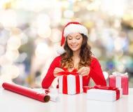 Mujer sonriente en regalos del embalaje del sombrero del ayudante de santa Foto de archivo libre de regalías