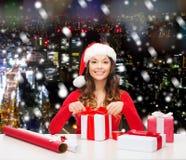 Mujer sonriente en regalos del embalaje del sombrero del ayudante de santa Fotografía de archivo libre de regalías