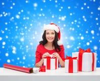 Mujer sonriente en regalos del embalaje del sombrero del ayudante de santa Imagen de archivo libre de regalías